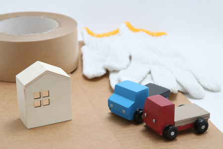 hauler: Toy mini car trucks, packing tape, card boards, cotton work gloves and house on white background. Distribution concept. Stock Photo