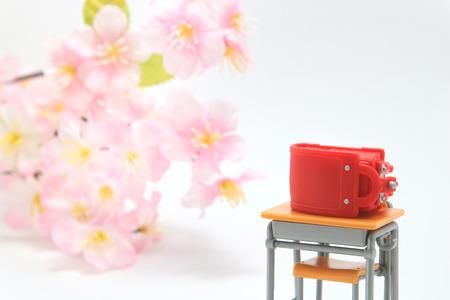 Schoolchilds rucksacks and cherry blossoms on white background. randoseru. Entrance ceremony consept.