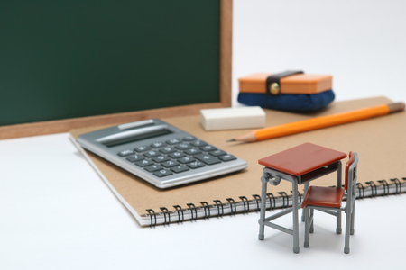 Miniature school desk, blackboard, calculator and notebook on white background. Education concept. Banque d'images