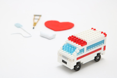 Toy ambulance car and abstract red heart on white background. Miniature drip, gibbs, and crutches.  Health, medicine, and cardiology concept. Health care, charity, donation concept.