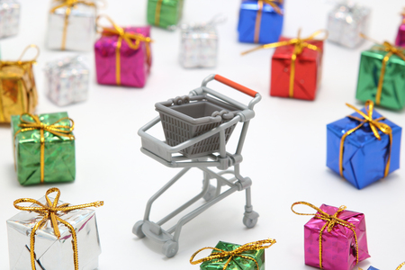 Steel shopping cart and colorful gift boxes on white background. Buying presents concept. Stock Photo