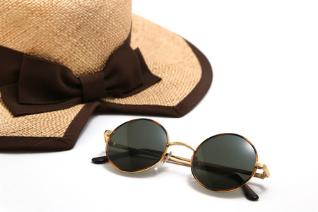 Straw hat and sunglasses on a white background. Summer concept. Stock Photo