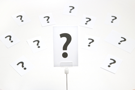 Big question mark on a piece of paper on white background. Many question marks on paper. Question concept.