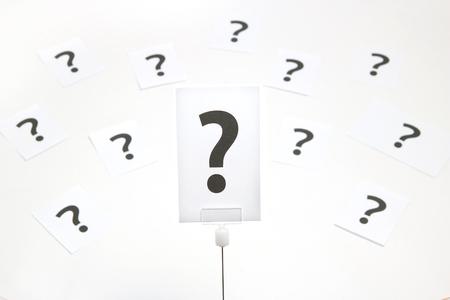 Groot vraagteken op een stuk papier op witte achtergrond. Veel vraagtekens op papier. Vraag concept.