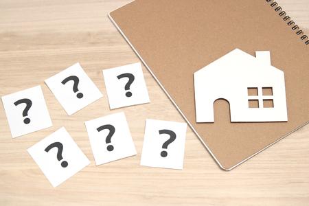 ミニチュアの家、白い紙に多くの疑問符。感嘆符の付いた家。不動産の概念。