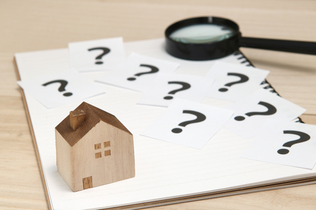 Miniature house and many question marks on white papers. House with question marks and magnifying glass. Real Estate Concept. Banque d'images