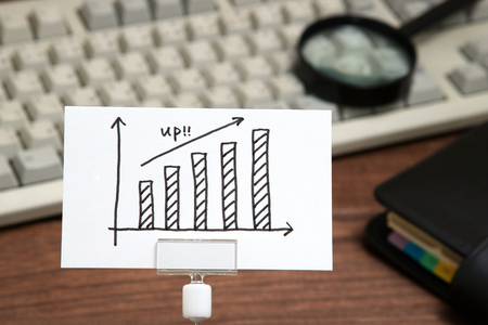 Growth Graph drawn on paper in front of computer keyboard and magnifying glass. Business growth concept.