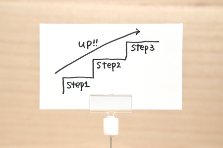 紙の上の矢印を上向きに手書き階段見出し。ビジネス成功の概念と成長のアイデア。