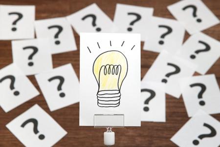 電球は多くの疑問符と白い紙の上に描画されます。ソリューションの概念。