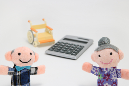 Elderly people with wheelchair and calculator on white background. Plans for retirement living concept. Фото со стока