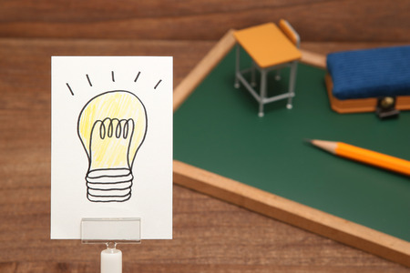 Light bulb drawn on white paper with the study tools as the background. Concept of learning inspiration.