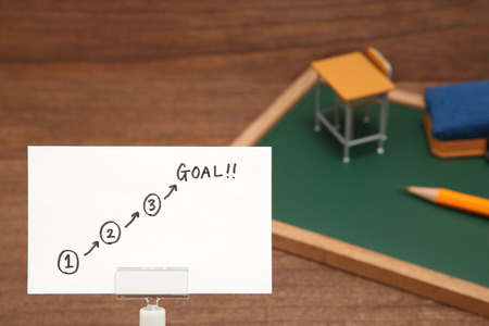 Start and Goal written on paper with the study tool as the background. Concept of step up of learning. 스톡 콘텐츠