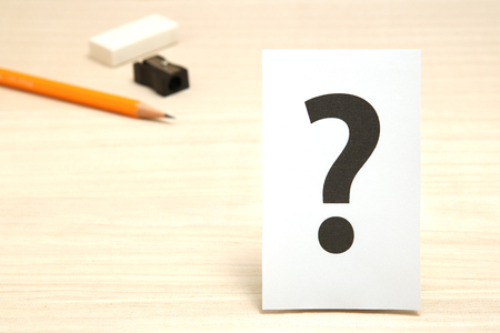 Big question mark on white paper, and stationery as the background. Concept of learning question.
