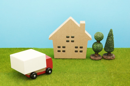 hauler: Toy car truck and house on green grass. Logistics, distribution, and delivery concept.