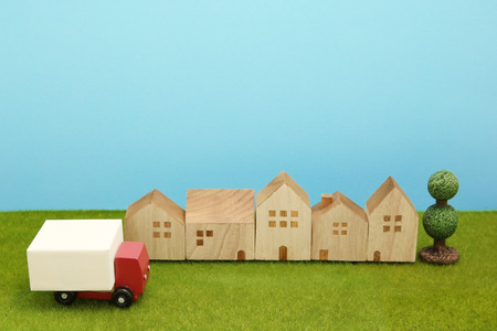 hauler: Toy car truck and houses on green grass. Logistics, distribution, and delivery concept. Stock Photo