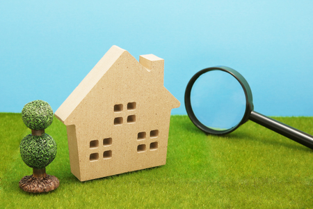 House and magnifying glass on green grass. House searching concept.