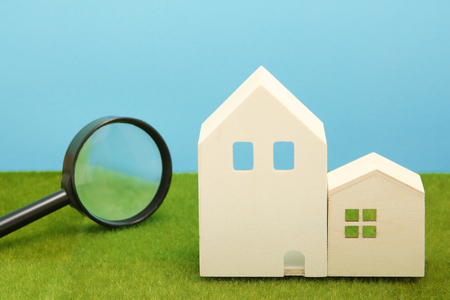 Houses and magnifying glass on green grass. House searching concept.