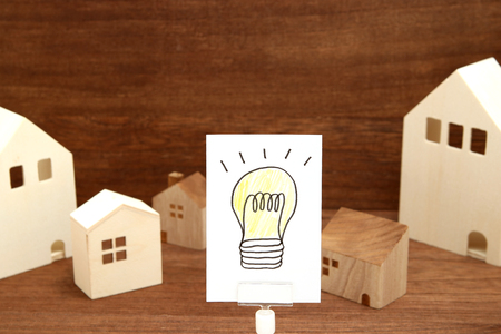 Handwritten bulb illustration and houses on wood. Eco technology and energy concept. Reklamní fotografie