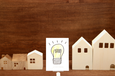 Handwritten bulb illustration and houses on wood. Eco technology and energy concept. Stock Photo