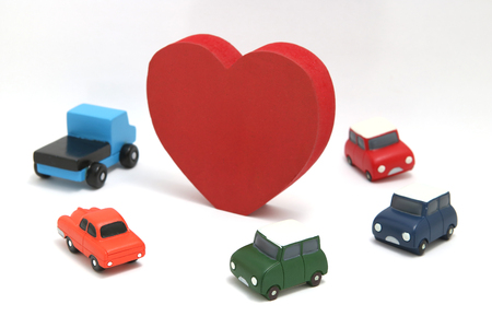 Some red hearts and cars on white background. Safe driving concept. Stock Photo