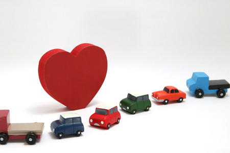 Red heart and cars on white background. Safe driving concept.