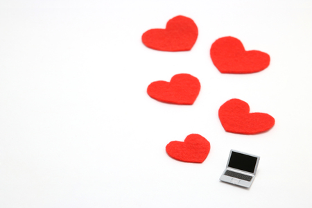 Miniature laptop and some red hearts on white background. Concept of love using a personal computer.