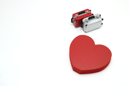 Miniature two suitcases and a red heart on white background. Concept of honeymoon.