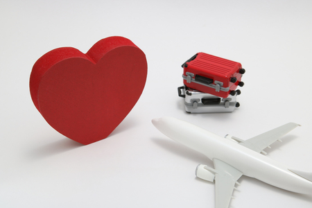Miniature two suitcases, airplane toy, and a red heart on white background. Concept of honeymoon by airplane.