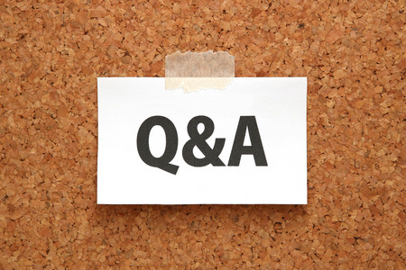 Q & A or Questions and Answers on a piece of white paper on a brown cork board. Q & A or Questions and Answers concept.