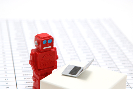 Robot or artificial intelligence and laptop on the number of tables in the document. Concept of artificial intelligence.