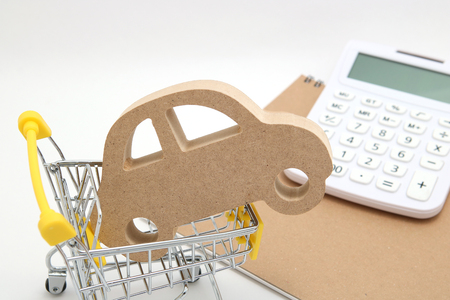 Miniature wooden car, shopping cart and calculator on white background. Concept of buying new car.