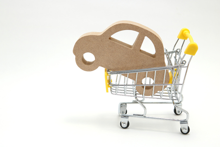 Miniature wooden car and shopping cart on white background. Concept of buying new car. Banque d'images