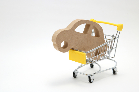 Miniature wooden car and shopping cart on white background. Concept of buying new car. Stock Photo