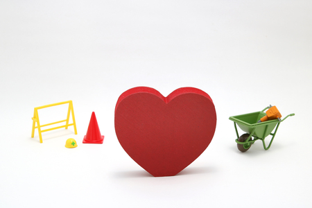 Concept of safety image. Red heart shaped wood and construction tools of miniature on white back ground. Banque d'images