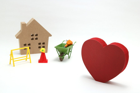 Concept of safety image. Red heart shaped wood, house and construction tools of miniature on white back ground. Banque d'images