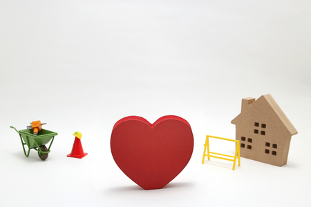 Concept of safety image. Red heart shaped wood, house and construction tools of miniature on white back ground. Stock Photo