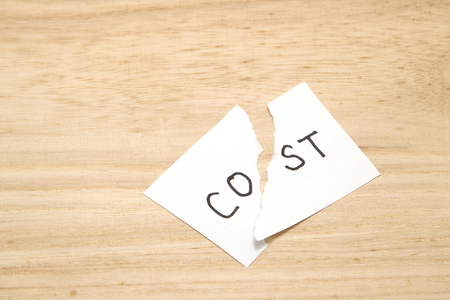 Cut the word cost concept for recession or credit crisis on wood.