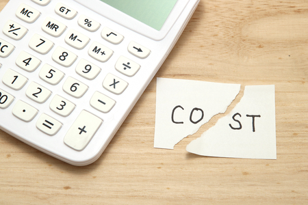 Cut the word cost concept for recession or credit crisis and calculator on wood. Concept of cost cut.