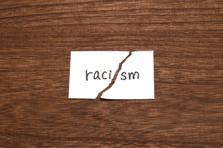 The paper written as racism is torn on wood. Concept of abolition of racial discrimination.