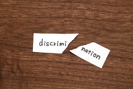 La carta scritta come discriminazione è strappata su legno. Concetto di abolizione della discriminazione.