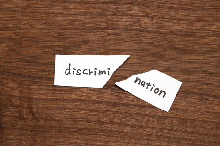 The paper written as discrimination is torn on wood. Concept of abolition of discrimination. Stockfoto