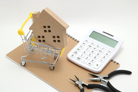 Miniature house, shopping cart, calculator and tools on white background. Concept of buying new house, real estate and renovation. Фото со стока