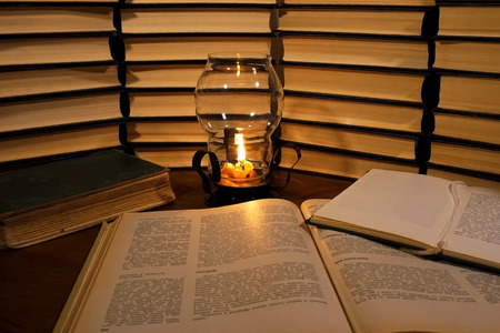Book and Candle. Candle and old books. Books stacked. Many books piles