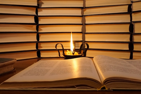 Open book and a burning candle. Lighted candle in an old candlestick on a books background. Reading a book by candlelight 스톡 콘텐츠