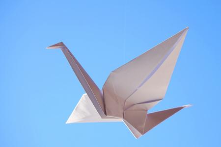 Origami bird. Flying origami bird on blue background