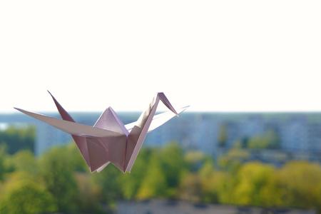 Origami crane. Paper bird on a blue sky background