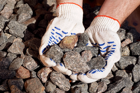 Crushed stone in hands. Crushed rock in the hands of a worker