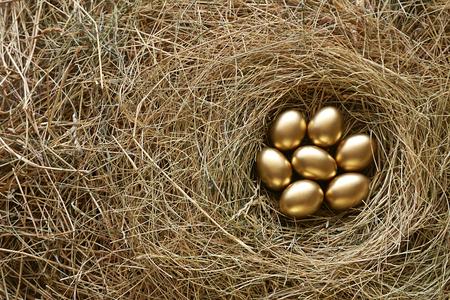 Golden eggs in nest. Straw background 스톡 콘텐츠