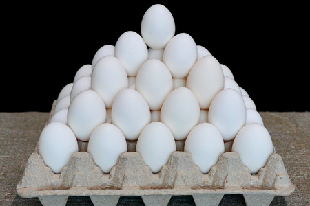 White chicken eggs. Pyramid from chicken eggs