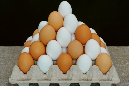 White eggs and brown eggs. Pyramid from chicken eggs